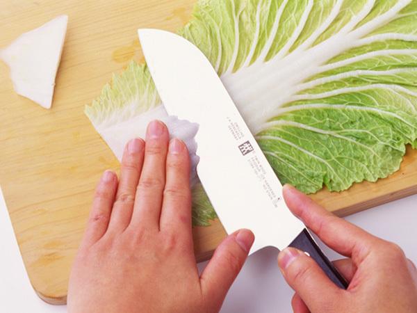 白菜のそぎ切り 包丁を斜め下に向かって寝かせて入れてから、そのまま手前にすっと引くようにして切る。