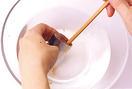 腹の中に残ったはらわたや汚れを洗います。水をはったボールの中で、菜箸の太いほうを骨にそって細かく動かしながら汚れをこすり落として。その後、ペーパータオルで表面と腹の内側の水けを拭き取れば、下ごしらえは完了。