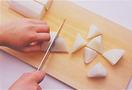 煮ものにするときは、乱切りにすると切り口の面が多くなり、味がしっかりしみ込みます。まず、縦4等分に切ってから、包丁を斜めに入れて最初の1切れを切ります。そのまま包丁は動かさず、大根の向きを90度ずつ変えながら斜めに切っていって。このとき、前の切り口の真ん中あたりに包丁を入れるようにすると、大きさが均一にそろいます。