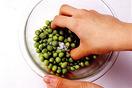 取り出した豆をボールに入れ、塩少々をふって手でかるくもみます。こうして加熱する前に塩をまぶしておくと、色鮮やかに仕上がるうえ、グリーンピース特有の臭みも取れます。
