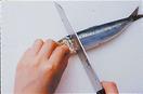 胸びれを手でつまみ、胸びれのつけ根から包丁を入れます。骨に当たったら刃を一気に下ろし、胸びれとともに頭を切り落とします。