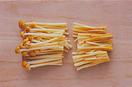 えのきは袋ごと根元の部分を切り落とし、長さを半分に切ってほぐす。