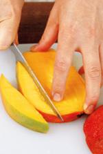 マンゴーは種を避けて縦3つに切る。種のまわりの果肉は種を避けて切り取り(写真)、皮をむいて1~1.5cm角に切る。種のついていない果肉は皮をむき、1~1.5cm角に切る。