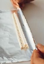 しんを作る。割り箸を2ぜん用意し、1本ずつに割る。キッチンばさみで長さ16~17cmのところに切り込みを入れ、手で折る。アルミホイルを30cm四方に切って広げ、手前に割り箸4本をまとめてのせ、くるくると巻く。アルミホイルの両端をねじって留め、サラダ油少々を表面全体に塗る。