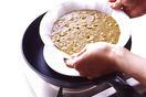直径26cmくらいのフライパンに、直径20cmくらいの耐熱の平たい皿を入れ、その上に生地を流し入れた器を置く。器の高さの半分くらいまで、フライパンの縁から熱湯を静かに注ぎ入れる。弱火にかけ、ふたをして25分ほど蒸し焼きにする。中心に竹串を刺してみて、生っぽい生地がついてこなければ蒸し上がり。器を取り出して粗熱を取り、オーブン用シートをはがして食べやすく切る。