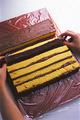 調理台(または大きめのまな板)の上に、30×50cmくらいに切ったラップを縦長に置く。カステラの茶色い面を上にして横に並べ、上面にココアクリームの1/3量をバターナイフなどで塗る。手前のカステラから順に手前に倒し、クリームを塗った面が隣のカステラと密着するように並べていく。すべて倒したら手前と左右の端を1cm、奥は3cmほど残して、上面に残りのココアクリームを塗る。