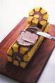 作り方1を参照して、同量の材料で同様に飾り用のココアクリームを作る。冷蔵庫からケーキを取り出し、ラップをはずして、端から5~6cmのところに包丁を寝かせて入れ、斜めに切り分ける。切り分けた部分の切り口の反対側の面に、ココアクリーム大さじ2を塗り、その面を下にしてケーキの端にのせる。さらに残りのココアクリームをケーキにのせ、切り口を残してバターナイフなどで広げるようにして全体に塗る。