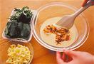キムチは汁けがあればきり、食べやすく切る。春菊は葉を摘む。たねを作る。ボールに卵を割りほぐし、水1/4カップを加えて混ぜる。小麦粉1/2カップ、片栗粉大さじ3を一度に加え、泡立て器で粉っぽさがなくなるまでよく混ぜる。キムチ、春菊、ピザ用チーズを順に加え、ゴムべらでさっくりと混ぜ合わせる。