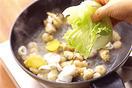フライパンにごま油大さじ2を中火で熱し、しょうがを入れて炒める。香りが立ったらシーフードミックスを凍ったまま加えて炒め合わせる。油がなじんだら水1と1/2カップを注ぎ、鶏ガラスープの素と、塩小さじ1/2を加える。ひと煮立ちしたらレタスを1枚ずつ6つ~8つにちぎって入れ、さらに、ねぎ、豆乳を加えてそのまま弱火にかけておく。