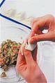 餃子の皮の中央に、たねの1/30量(ティースプーン1杯くらいが目安)をのせる。指で皮の縁にぐるりと水をつけ、皮を2つ折りにするようにたたみながら、途中親指を入れて大きくひだを寄せて閉じる。