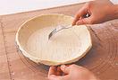 パイシートをパイ皿の上にのせ、皿より大きめに縁を切って敷き込み、余分な生地を切る。縁からはみ出た分を指先でつまんで1cmくらい高くする。パイの底部分にフォークの先で全体にまんべんなく穴をあけてオーブン用シートをのせ、底がふくらまないようにひとまわり小さい耐熱容器を置く。190~200℃のオーブンで12~15分焼き、いったん取り出す。オーブン用シートごと耐熱容器をはずして、さらに12~15分焼いてさます。