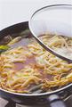 うどんを加えて煮る  フライパンのあいたところに、具を押し広げながら、冷凍うどんを重ならないように並べ入れる。こうしてあいたところにうどんを加えるようにすると、煮汁に浸りやすくなる。めんつゆと水2と1/2カップを加え、ふたをして中火のまま煮る。煮立ったらふたを取り、うどんを菜箸でほぐしながら全体を混ぜ、器に盛る。