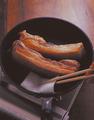 フライパンを中火で熱し、豚肉を脂身のほうを下にして並べ入れ、こんがりと焼き色がついたら裏返す。豚肉から出る脂をときどきペーパータオルで拭き取りながら、側面も同様に焼きつけ、全面に焼き色をつける。