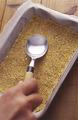 バットに【2】を入れ、スプーンで押さえて平らに敷きつめ、冷蔵庫に入れて冷やす。オーブンを160℃に温めはじめる。
