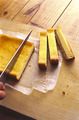 まな板にのせ、側面のオーブン用シートをはがしてから、横に幅1.5~2cmに切る。