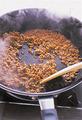 にんにく、豆板醤、ひき肉を順に入れて、ひき肉をほぐしながら炒める。肉がぽろぽろになったら、しょうゆ大さじ2、酒大さじ1、砂糖小さじ2を加えて混ぜ合わせる。スパゲティを戻し入れて全体を混ぜ、さらにレタスを加えてざっと混ぜる。器に盛り、白いりごまを散らす。