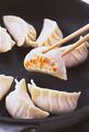 10個ずつ、2回に分けて焼く。フライパンにサラダ油大さじ1を中火で熱し、餃子をぐるりとドーナツ状に並べ入れて、底に焼き色がつくまで2分ほど焼く。