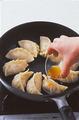 ふたを取り、フライパンを揺すりながら余分な水けをとばす。水けがなくなったらごま油大さじ1を餃子に回しかける。餃子を少し持ち上げてみて、底全体にこんがりと焼き色がついていたら焼き上がり。器に取り出し、フライパンをペーパータオルでさっと拭いて、残りも同様に焼く。