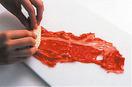 まな板に牛肉1枚を縦長に広げ、塩、こしょう各少々をふる。手前にフライドポテトの1/5量を凍ったまま横向きにのせ、向こう側まで巻く。残りも同様にして巻き、小麦粉を薄くまぶしつける。