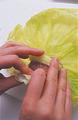 しんを切り落とした三角形の二辺を重ね合わせ、たね1つをのせる。さらに切り落としたしんをたねの上にのせ、手前から包むようにして、ひと巻きする。