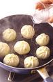 直径26cmのフライパンにサラダ油大さじ2/3を中火で熱し、肉まんを2~3cm間隔で並べる。水2/3~1カップを注ぎ、ふたをして中火で3分ほど蒸し焼きにする。