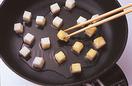 フライパンにごま油大さじ4を中火で熱して、餅を間隔をあけて並べ、両面に焼き色をつける。そばは、たっぷりの湯で袋の表示どおりにゆで、ざるに上げて流水で手早く洗う。