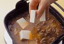鍋にごま油大さじ1と1/2を入れて中火で熱し、牛肉、キムチ、にんにくを2~3分炒める。スープと残りの煮汁用調味料を加えて4~5分煮たら、豆腐、にらを加えてひと煮する。