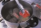 厚手の鍋にオリーブオイルを中火で熱し、牛すね肉と豚スペアリブを入れて、全体にこんがりと焼き色がつくまで焼いて取り出す。鍋に残った脂を、鍋底にうっすらたまるくらい残して捨て、にんじん、セロリ、玉ねぎを入れ、しんなりとするまで弱火で20~30分炒める。