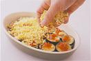 耐熱皿の内側にオリーブオイルを薄く塗り、トマトソースの1/3量を入れて全体に広げる。揚げたなすの1/2量を重ならないように並べ、残りのトマトソースの1/2量を全体に広げ、残りのなすを重ねる。刻んだ卵を全体に散らして塩、こしょう各少々をふり、ピザ用チーズも同様に散らして、残りのトマトソースを広げる。200℃のオーブンで、チーズが溶け、こんがりと焼き色がつくまで15分ほど焼く。