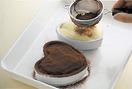 残りのハート形のスポンジを1切れずつ重ね、すきまがあれば、同様に残りのスポンジをちぎって詰める。ラム酒を塗り、残りのチーズクリームを1/4量ずつのせてならす。仕上げ用のココアパウダーを茶こしを通して表面全体にふりかけ、冷蔵庫で1時間ほど冷やす。