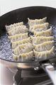 フライパンにサラダ油少々を強めの中火で熱し、餃子の1/2量を並べる。すぐに熱湯1/2カップを加えてふたをし、強めの中火のまま4~5分蒸し焼きにする。