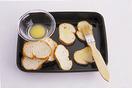 バターを耐熱の器に入れてラップをかけ、電子レンジで15秒ほど加熱して溶かす。刷毛(なければスプーン)で、フランスパンの表面全体にバターを塗る。