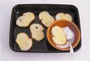 グラニュー糖を小さめの器に入れる。フランスパンのバターを塗った面に、スプーンでかけるようにして、全体にグラニュー糖をまぶす。