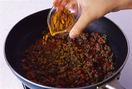 フライパンにサラダ油大さじ1/2を中火で熱し、ひき肉を入れる。木べらでほぐしながら炒め、色が変わってぽろぽろになったら、赤ピーマンを加える。さっと炒め、カレー粉を加えて全体にからめる。