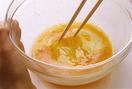 ボールに卵を割り入れ、菜箸を底につけたまま左右に動かし、泡立てないように混ぜる。砂糖小さじ5、酒小さじ2、塩小さじ1/3を加えて混ぜ合わせ、万能こし器でこす。