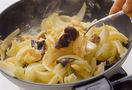 そのまま10秒ほどおいてから、スプーンで上下を返すように全体を大きく混ぜる。卵はすぐに混ぜず、しばらく火が通るのを待って。半熟のうちに、スプーンで大きく混ぜて、火を通しすぎないようにします。卵がふんわりと固まったら火を止め、器に盛って香菜を散らす。