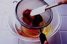 いちごの甘煮を、万能こし器を通して寒天液のボールにこしながら加え、混ぜる。大きめのボールに氷水を用意し、寒天液のボールの底を当てる。ゴムべらで底から混ぜながら、粗熱を取る。