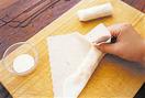 小さめの器に、小麦粉、水各大さじ1を混ぜ合わせて、のりを作る。春巻きの皮1枚を、角が正面にくるように置き、真ん中よりやや手前に、たねの1/8量を横長に広げてのせる。まず手前の皮をたねにかぶせるように折ってひと巻きし、右、左の順に皮をたねにかぶせるように折る。中に空気が入らないように、手前からしっかりと巻き、巻き終わりに、のりを少量つけて留める。残りも同様に作る。