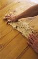 生地をのし台(またはきれいに拭いた調理台やテーブル)に移し、片方の手で生地の手前を押さえ、もう片方の手で生地を手前から向こうにギュッと押しながらのばす。