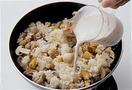ご飯を加え、全体をほぐすように炒める。全体が混ざったら、牛乳2カップを注ぎ入れ、塩、こしょう各少々、にんにくのすりおろしを入れて味をととのえ、ひと煮立ちさせる。器に等分に盛り、粗びき黒こしょう適宜をふる。