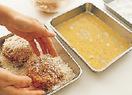 たねを4等分し、厚さ1.5cmくらいの平らな円形に形作る。残りの卵はバットに溶きほぐす。たねに小麦粉、溶き卵、パン粉の順にころもをつける。