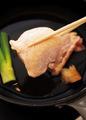 鶏肉は横半分に切る。フライパンに鶏肉、ねぎの青い部分、しょうがの皮と、水1/2カップ、酒大さじ1を入れてふたをし、中火にかける。4~5分蒸して裏返し、さらに4~5分蒸す。取り出して粗熱を取り、横に幅2cmに切って器に盛る。