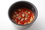 炊飯器の内がまに米を入れ、【3】【4】と、塩小さじ2/3、粗びき黒こしょう少々を入れてさっと混ぜる。殻からはずしたあさり、トマトを散らして、普通に炊く。炊き上がったらバター10g、殻つきのあさりを加えてさっくりと混ぜる。器に盛り、イタリアンパセリをふる。