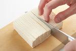 豆腐は横に厚さ1cmに切り、ペーパータオルにはさんで水けを拭く。