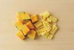 かぼちゃは種とわたを取り、ところどころ皮をむいて2cm角に切る。とうもろこしは包丁で粒をそぎ取る。