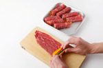 牛肉は1枚ずつ縦に広げて並べ、塩、粗びき黒こしょう各少々をふる。ゴーヤー、赤パプリカ、黄パプリカをそれぞれ1/8量ずつ牛肉の手前にのせてきっちりと巻き、巻き終わりを下にして置く。小麦粉を薄くまぶす。