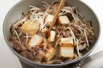 同じフライパンに、にんにく、豚肉を入れてさっと炒める。肉の色が変わったら、玉ねぎ、まいたけを加えて炒め、しんなりしたら、豆腐、もやしを入れ、豆腐をかるくくずすように炒め合わせる。しょうゆ大さじ1と1/2を鍋肌から回し入れ、万能ねぎを加え、削り節の1/2量をふって炒め合わせる。器に盛り、残りの削り節をのせる。