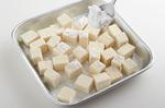 豆腐は2cm角に切ってペーパータオルで包んで5分ほどおき、水けをきる。塩少々をふり、小麦粉大さじ3をまぶす。じゃがいもはよく洗い、皮つきのまま縦12等分のくし形に切る。にんにくは横に薄切りにする。オニオンソースの材料を小さい器に合わせる。