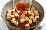 続けて豆腐を並べ入れ、全体をこんがりと焼き、余分な油をペーパータオルで拭いてから、オニオンソースを回し入れてからめる。器に盛り、にんにくを散らし、粗びき黒こしょう適宜をふる。じゃがいも、パセリを添える。