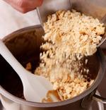 <b>黒砂糖を溶かし、油、おから、ごまを加える</b> オーブンを再び170℃に予熱する。鍋に黒砂糖と、水大さじ2を入れて中火にかけ、耐熱のゴムべらで粒をつぶしながら1~2分熱する。ふつふつと煮立ってきたら火を止め、菜種油を加えて混ぜる。さらにドライおから、白いりごまを加え、全体をまんべんなく混ぜ合わせる。